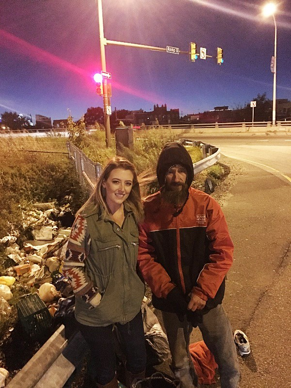 Image: Kate McClure stands with Johnny, the homeless man that gave her his last 20 dollars to fill her car with gas when it broke down on the side of I-95. Kate is trying to raise money for Johnny so he can get back on his feet.