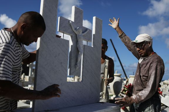 A group of workers repair a gravestone damaged by Hurricane Maria in the immediate aftermath of Hurricane Maria.