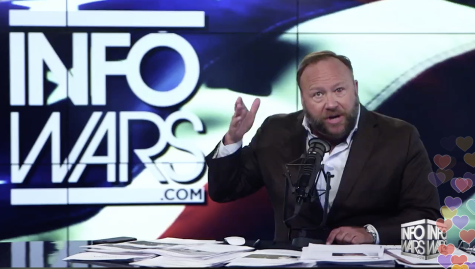 Alex Jones gestures with his hands at his broadcast desk.