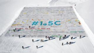 """The postcard, seen from above on the snow, reads: """"#1.5C - Stop global warming"""". People walking underneath it look tiny by comparison, emphasising the scale."""