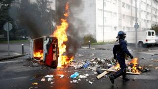 "A French riot policeman walks past a burning car as youth and high school students protest against the French government""s reform plan, in Nantes, France, December 6, 2018"