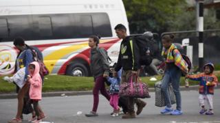 Venezuelan migrants walk out a bus terminal heading to an improvised camp in Bogota