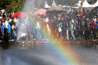 People queue to drink fresh water from a burst pipe at Uhuru Park during Christmas Day Celebrations in Nairobi, Kenya December 25, 2018.