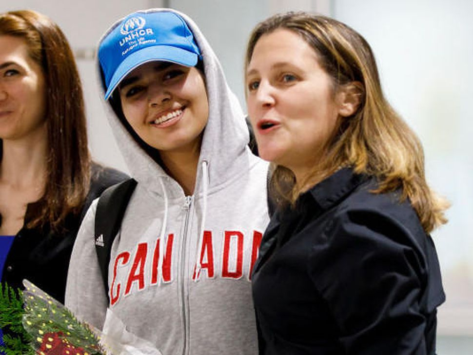 Rahaf Mohammed al-Qunun, in cap, smiles as she's introduced to the media at Toronto Pearson International Airport, alongside Canadian Minister of Foreign Affairs Chrystia Freeland.