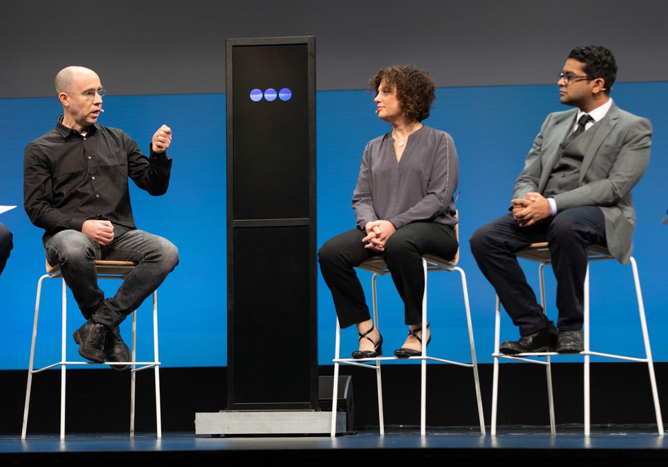 Humans discussed IBM's AI debate technology at a contest touting the tech. From left to right: Noam Slonim, Project Debater's principal investigator at IBM Research; IBM's Project Debater screen; Ranit Aharonov, IBM's manager of Project Debater; and Harish Natarajan, the grand finalist at the 2016 World Debating Championships.