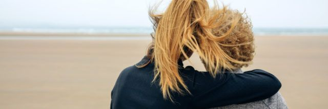 Back view of senior and young woman looking at sea on the beach in autumn