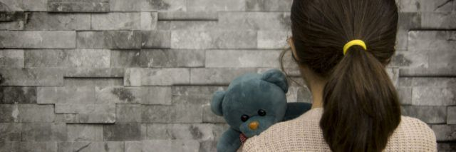little girl holding a teddy near looking at a brick wall