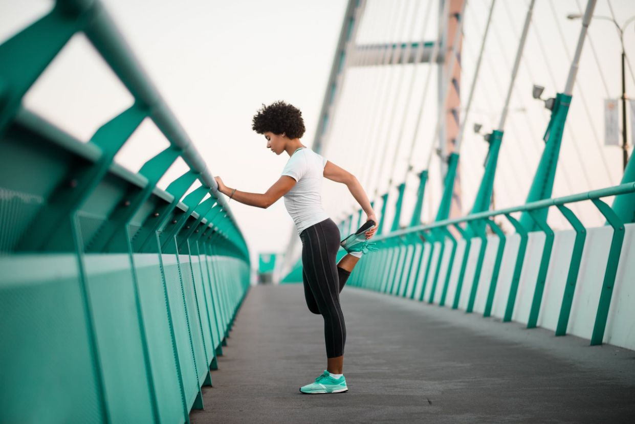 Healthy young slim fitness girl warming up on bridge