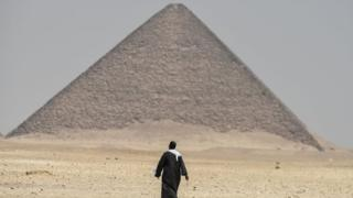 A man walks next to the Red Pyramid at Dahshur. Photo: 13 July 2019