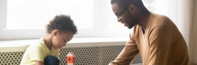 father in glasses and adorable toddler son building constructor tower, loving black dad and little child playing with colorful wooden blocks, sitting on warm floor at home