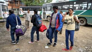 Tourists wait for buses to leave Kashmir on August 3