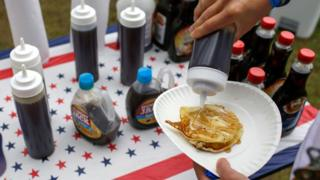 A man pouring maple syrup onto pancakes at the Polk County Steak Fry