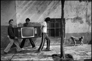 Men carrying a television in the street