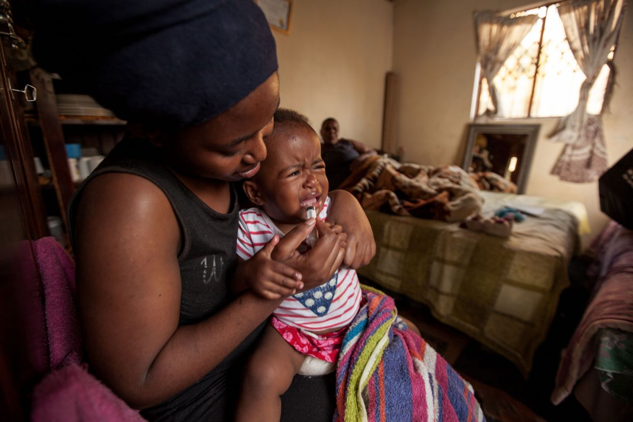 A mother in KwaMashu, South Africa, feeding her two-year-old the older, more common H.I.V. treatment, which contained 40 percent alcohol and had a bitter metallic taste that is hard to keep down. (Greg Lomas/DNDi via The New York Times)