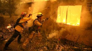 Firefighters try to keep flames from burning home from spreading to a neighbouring apartment complex as they battle the Camp Fire in November 2018