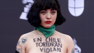 """Mon Laferte pictured with the words """"in Chile they torture, rape and kill""""."""