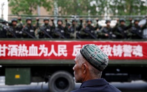 <span>A Uighur man looks on as a truck carrying paramilitary policemen travel along a street during an anti-terrorism oath-taking rally in Urumqi, Xinjiang in 2014 </span> <span>Credit: REUTERS </span>