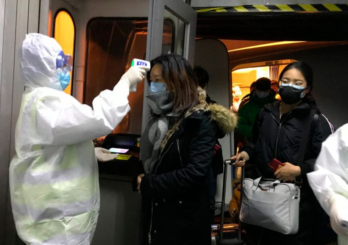 Health Officials in hazmat suits check body temperatures of passengers arriving from the city of Wuhan Wednesday, Jan. 22, 2020, at the airport in Beijing, China. Nearly two decades after the disastrously-handled SARS epidemic, China's more-open response to a new virus signals its growing confidence and a greater awareness of the pitfalls of censorship, even while the government is as authoritarian as ever. (AP Photo Emily Wang)