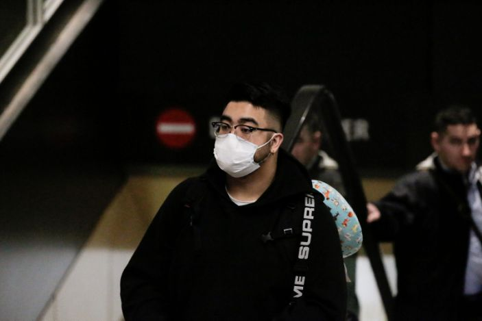 FILE PHOTO: A traveler wearing a mask arrives on a direct flight from China, after a spokesman from the U.S. Centers for Disease Control and Prevention (CDC) said a traveler from China had been the first person in the United States to be diagnosed with the Wuhan coronavirus, at Seattle-Tacoma International Airport in Washington, U.S. January 23, 2020. REUTERS/David Ryder/File Photo