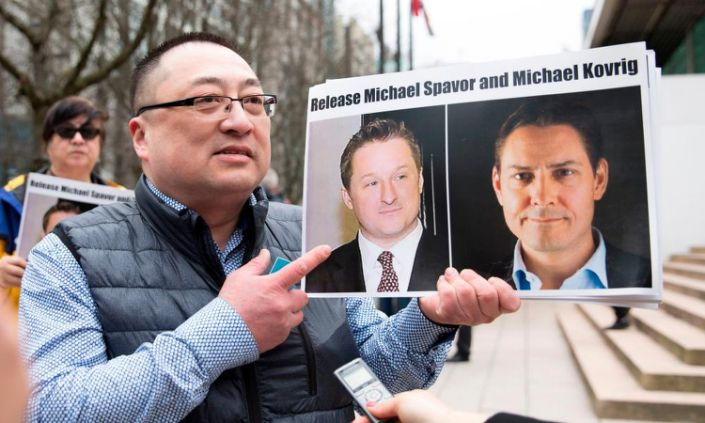 "<span class=""element-image__caption"">A protester holds photos of Canadians Michael Spavor and Michael Kovrig, who are being detained by China, in Vancouver.</span> <span class=""element-image__credit"">Photograph: Jason Redmond/AFP via Getty Images</span>"