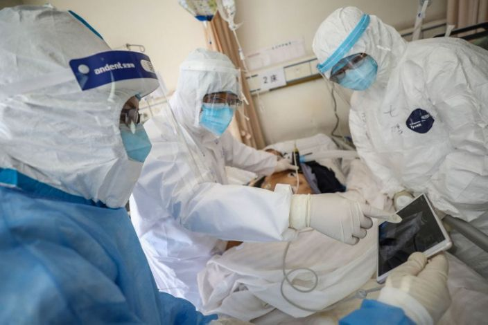 A doctor examines a patient who is infected by the coronavirus at a hospital in Wuhan in China's central Hubei province.