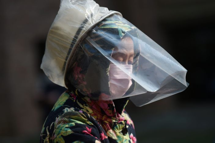 A woman dons a makeshift protective face shield at a residential compound in Wuhan, the epicenter of the novel coronavirus outbreak.