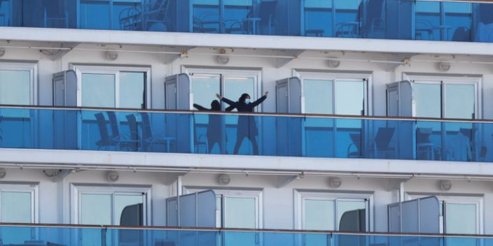 A passenger stretches on the balcony of a cabin of the cruise ship Diamond Princess on February 11, 2020.