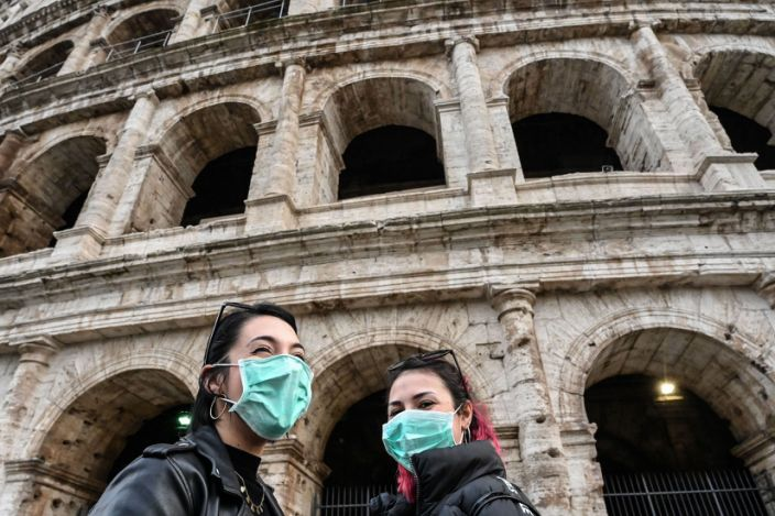 Italian tourists from Sardinia wear protective respiratory masks and tour outside the Colosseum in Rome on January 31, 2020.