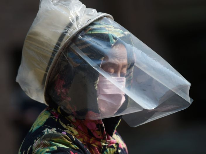 A woman dons a makeshift protective face shield at a residential compound in Hubei province, the epicenter of the novel coronavirus outbreak.