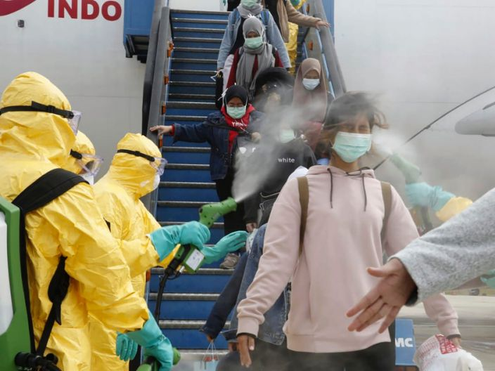 Indonesians arriving from Wuhan, China, are sprayed with antiseptic at Hang Nadim Airport in Batam, Indonesia on Sunday, February 2, 2020.