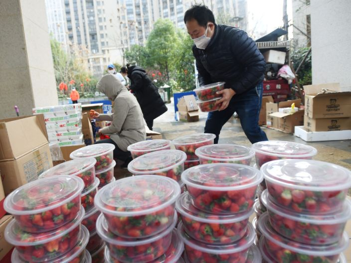 A man wearing a face masks sorts strawberries purchased by residents through group orders at a residential compound in Wuhan, Hubei province.