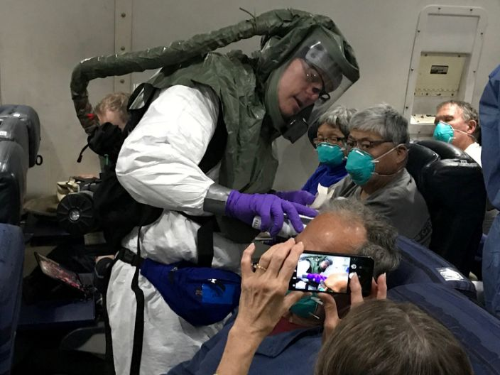 A worker in a protective suit checks the temperatures of passengers who were on board the Diamond Princess cruise ship, on a chartered evacuation aircraft from Japan's Tokyo International Haneda airport, en route to Lackland Air Force Base in San Antonio, Texas, US, on February 17, 2020.