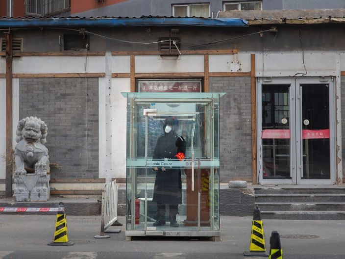 A security guard wearing a face mask stands in a glass cubicle on an empty street in Beijing, China, January 27, 2020.