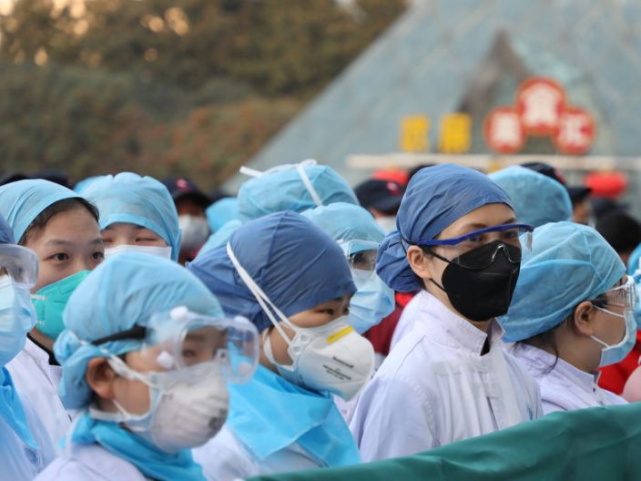 Medical staff rally before taking over a large temporary hospital built in an exhibition center in Wuhan, February 5, 2020.