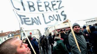 """Two men hold a banner that reads, """"free Jean Louis"""" as they rally in support of a farmer being prosecuted for the attempted murder of an alleged fuel thief, during a demonstration outside the court of appeal in Reims, northeastern France, on 13 February, 2020."""