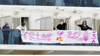 "Passengers display a banner reading ""Trump 2020"" on the deck of the cruise ship Diamond Princess, 14 February 2020"