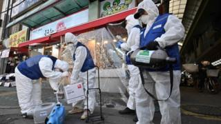 Workers from the Korea Pest Control Association, wearing protective gear, prepare to spray disinfectant to help prevent the spread of the novel coronavirus at a market in Seoul on February 24, 2020