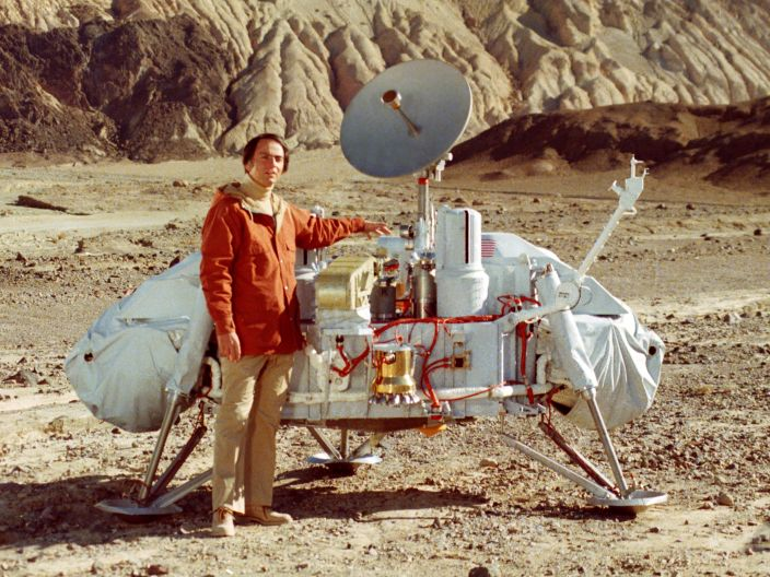"Dr. Carl Sagan, who is famous for his long career in astronomy as well as his television series ""Cosmos,"" poses with a model of the Viking lander in Death Valley, California."