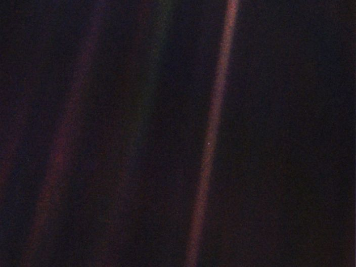 "In the original ""Pale Blue Dot"" image, released February 14, 1990, Earth is a bright speck within the sunbeam just right of center."