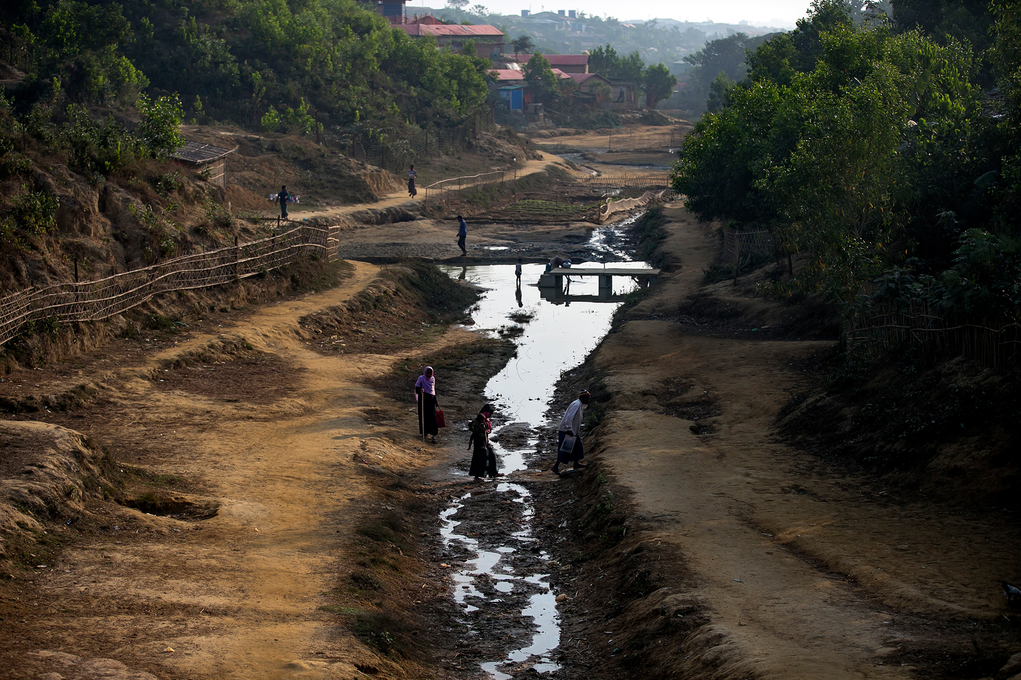 People cross a stream in a Rohingya refugee camp on January 23 in Cox's Bazar, Bangladesh.