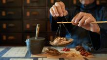 Man measuring ingredients in traditional Asian apothecary.
