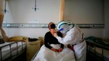 A patient infected by the COVID-19 coronavirus receives acupuncture treatment at Red Cross Hospital in Wuhan, China