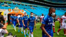 Players of Gremio enter the field wearing masks before the match against Sao Luiz.