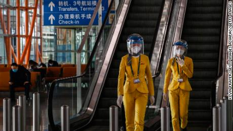 Staff wear protective masks and visors as they walk in the arrivals area at Beijing Capital International Airport on March 24.