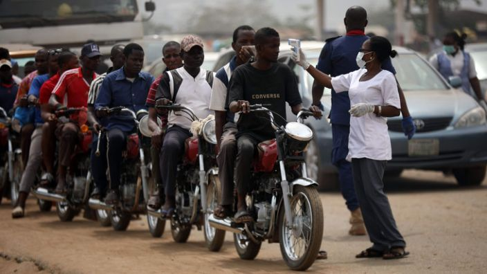 These motorbike riders were having their temperatures checked as they left Abuja