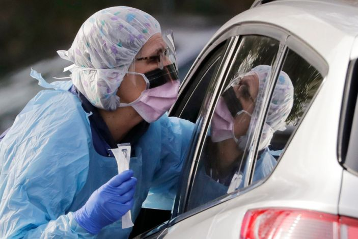 Laurie Kuypers, a registered nurse, takes a swab from a patient at a drive-through COVID-19 coronavirus testing station for University of Washington Medicine patients in Seattle.