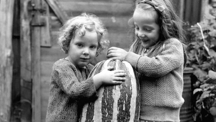 Two young girls with a marrow grown at at allotment in Surrey in 1941
