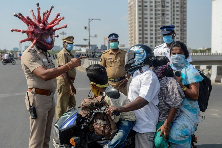 Police inspector Rajesh Babu (C) wearing coronavirus-themed helmet speaks to a family on a motorbike at a checkpoint during a government-imposed nationwide lockdown as a preventive measure against the COVID-19 coronavirus in Chennai on March 28, 2020. (Photo by Arun SANKAR / AFP) (Photo by ARUN SANKAR/AFP via Getty Images)