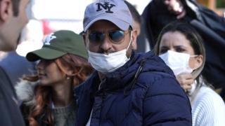 Visitors to New York City's theatre district wear face masks as a precaution