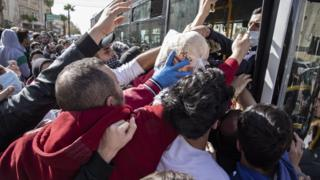 People try to collect bread from municipal buses in Amman, Jordan (24 March 2020)